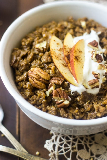 bowl of slow cooker oatmeal topped with nuts and apple slices