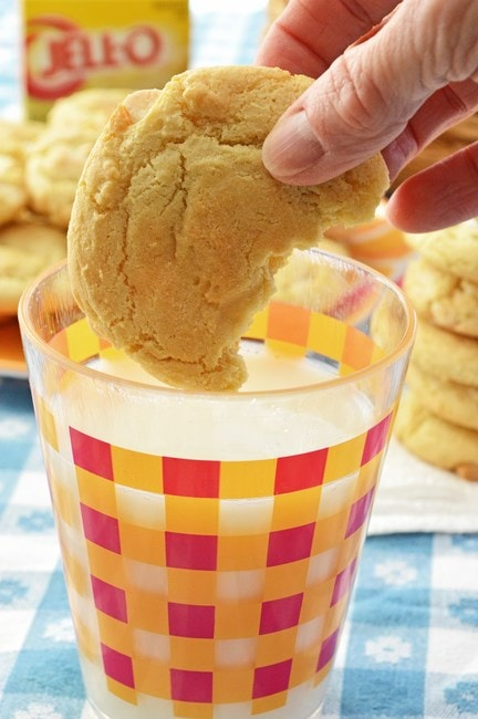 A lemon cream cheese cookie being dunked into a glass of milk.