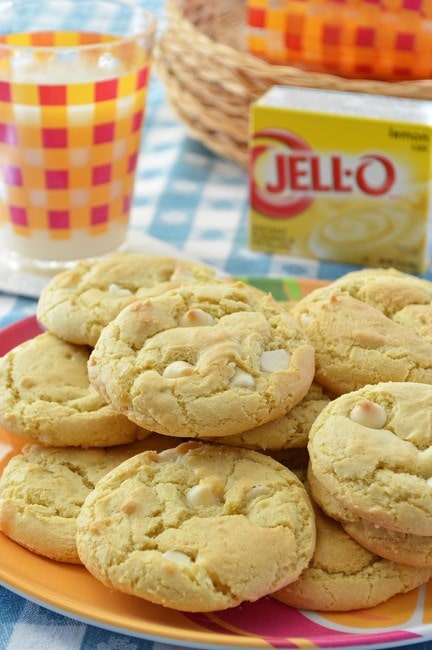 A plate of gluten-free lemon cookies, with a glass of milk and a package of lemon instant pudding mix in the background.
