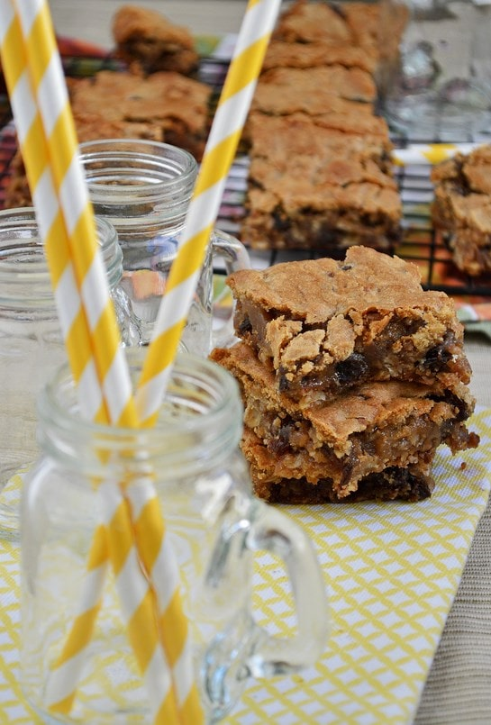 Sliced oatmeal raisin cookie bars on a wire rack and stacked on a napkin. A jar of straws rests in the foreground.