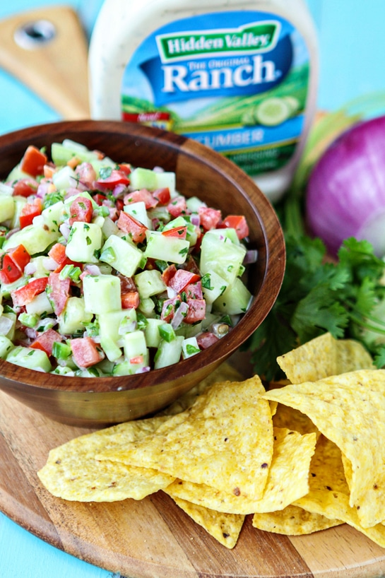 Creamy Cucumber Salsa in bowl on platter with chips, ranch dressing and cilantro