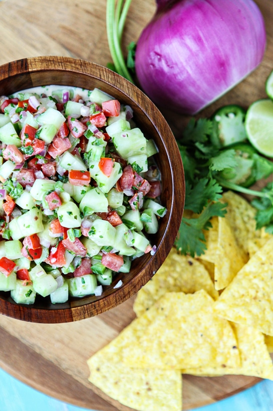 creamy cucumber salsa in wooden bowl next to chips and fresh veggies