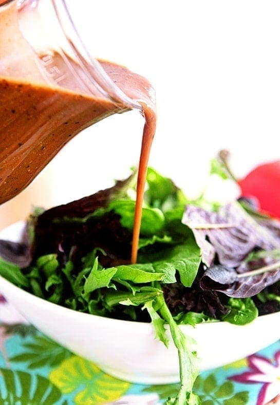 pouring creamy balsamic dressing onto a salad