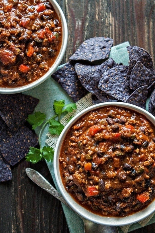 pumpkin and turkey black bean chili in two white bowls with blue tortilla chips