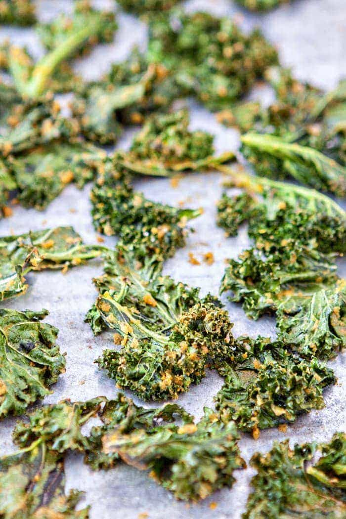 "These ""Cheesy"" Kale Chips are a great, healthy way to satisfy your cravings for something salty and cheesy. Nutritional yeast gives them a nutrient-rich cheesy flavor without any added dairy."