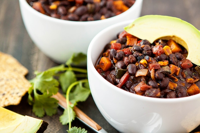 two bowls of butternut squash black bean chili garnished with avocado slices
