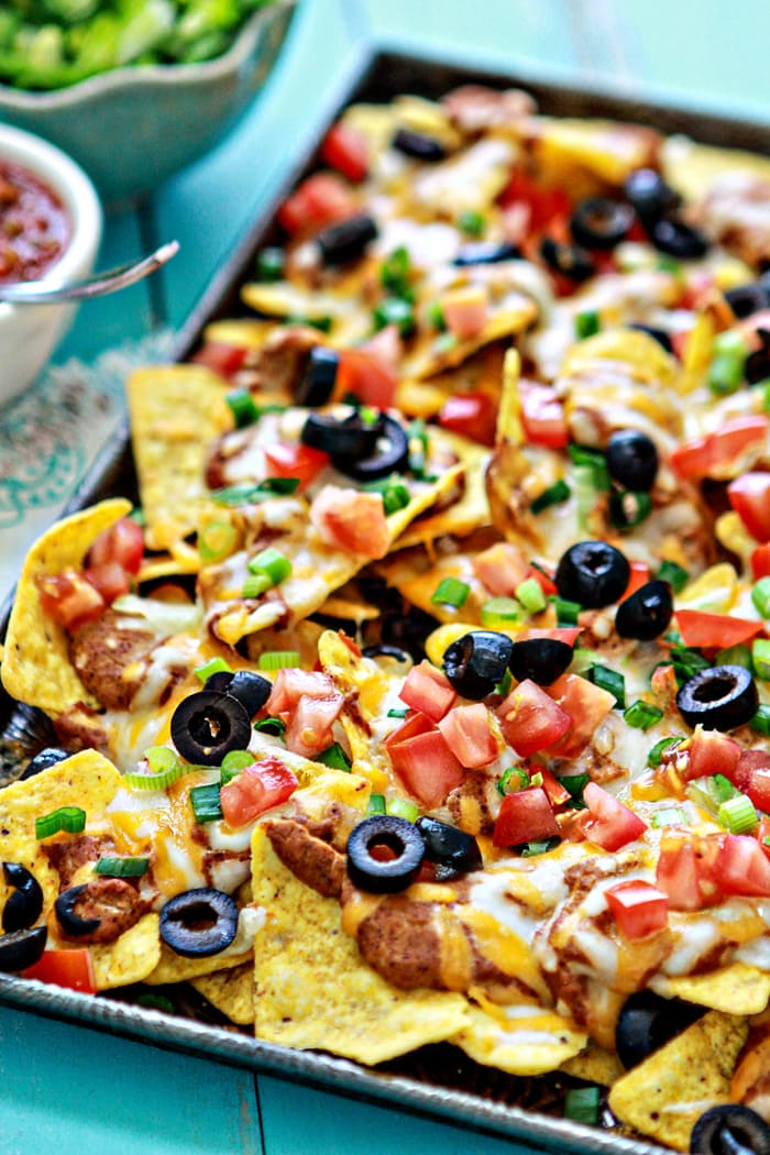 easy baked nachos topped with onion, tomatoes, and olives