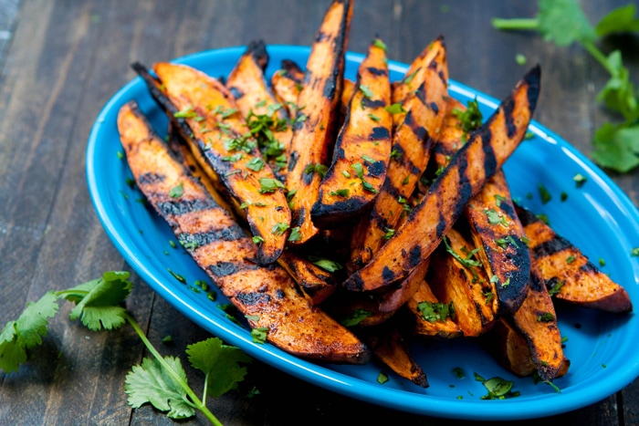 Grilled Sweet Potato Wedges sprinkled with cilantro on blue plate