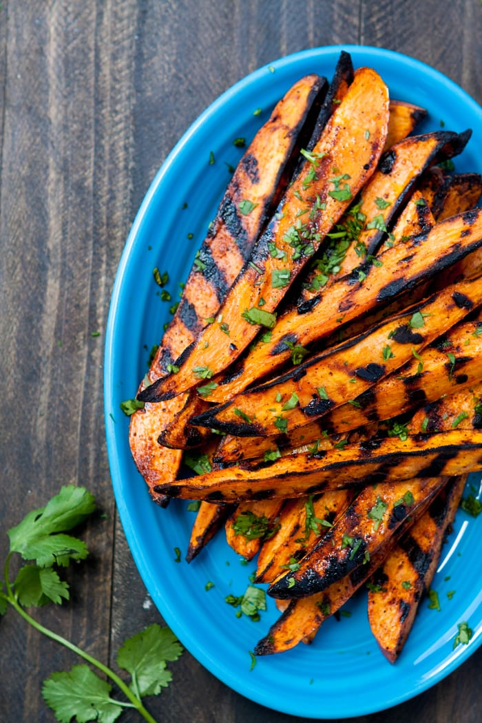 Grilled Sweet Potato Fries piled on blue plate with cilantro