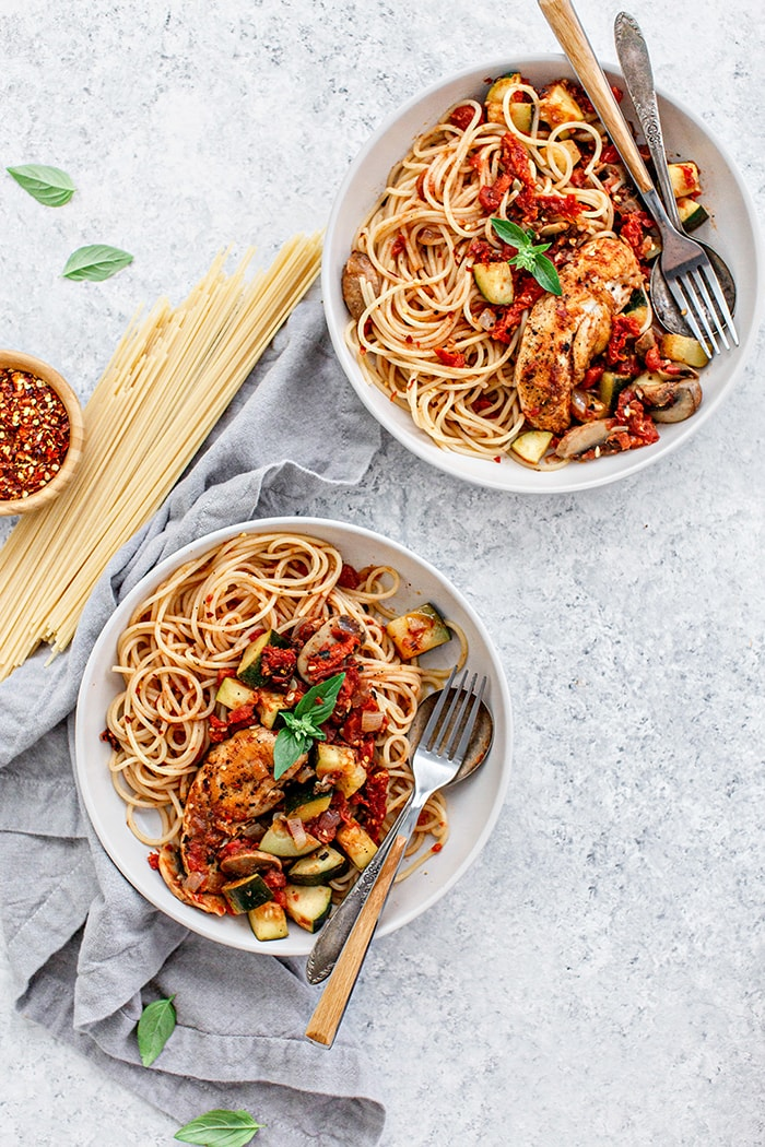 two white bowls of pasta with chicken and tomatoes