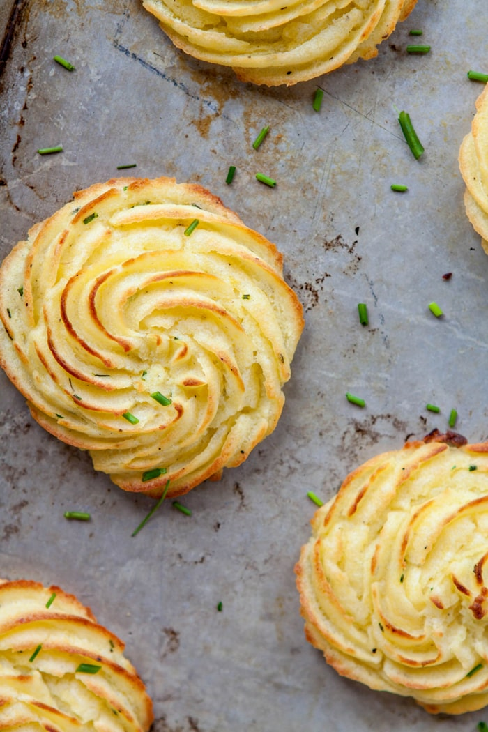 duchess potatoes garnished with fresh chives on baking tray