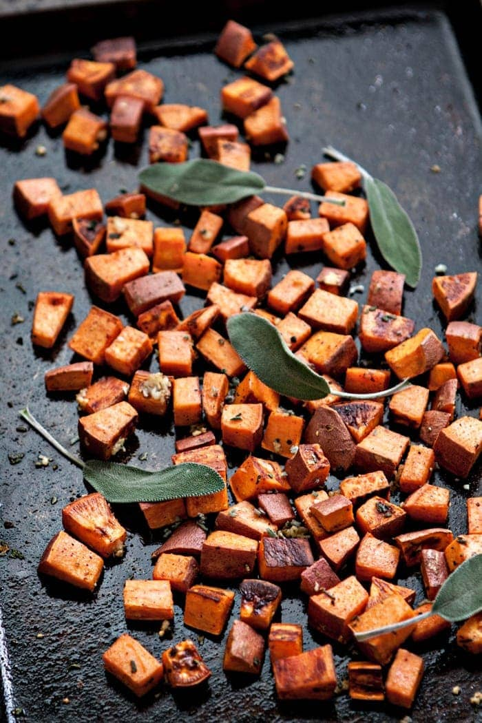 The Best Roasted Sweet Potatoes (with Garlic and Sage): Cubed sweet potatoes tossed in olive oil, salt, and pepper are roasted and then tossed generously with fresh garlic and sage. #sweetpotatoes #roastedpotatoes #roastedsweetpotatoes #sweetpotatorecipe