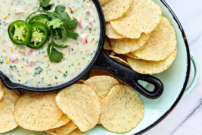 queso blanco dip in small skillet with tortilla chips