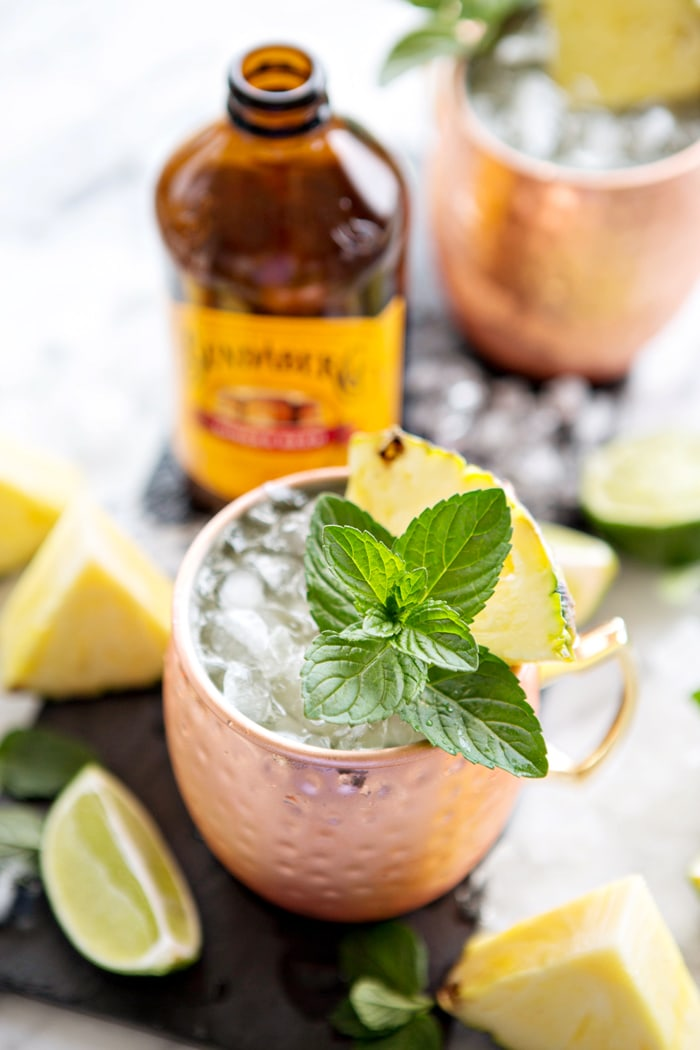 pineapple mint moscow mule in front of bottle of ginger beer