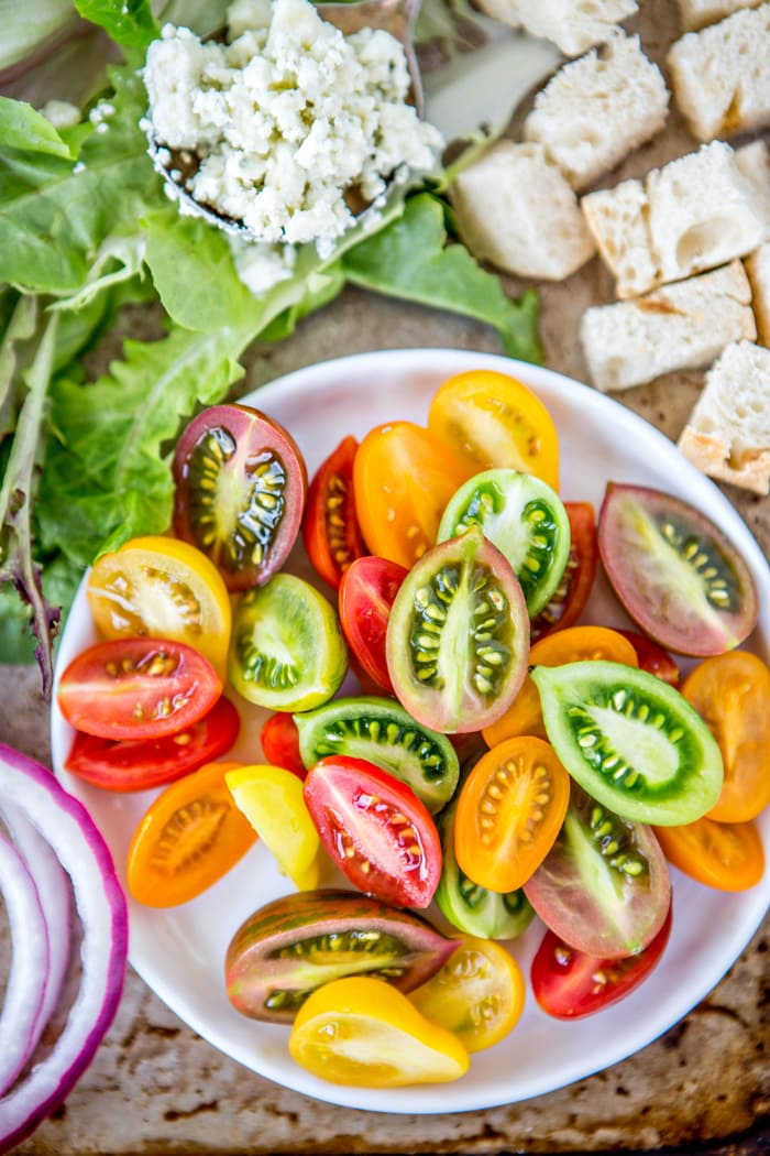 Chopped lettuce, heirloom baby tomatoes, plenty of bacon, bleu cheese, and cubes of toasted bread make up this Bleu Cheese BLT Salad, a fun take on a classic BLT