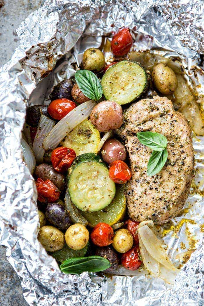 Pesto Pork Chop and Summer Vegetable Foil Dinners: Fresh, summertime vegetables are tossed in pesto and balsamic and cooked with boneless pork chops in this makeover version of the classic foil dinners from childhood.