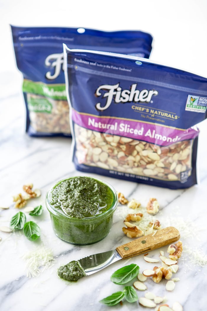 jar of walnut almond pesto with two bags of Fisher nuts