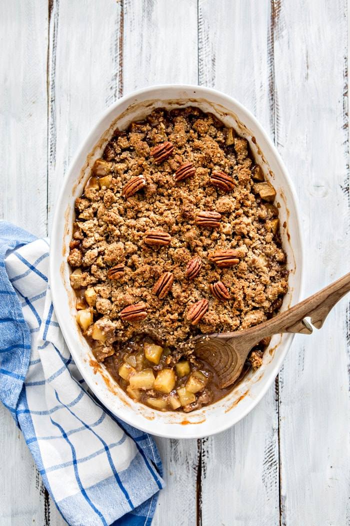 homemade apple crisp with oatmeal crumble topping in white baking dish with wooden spoon