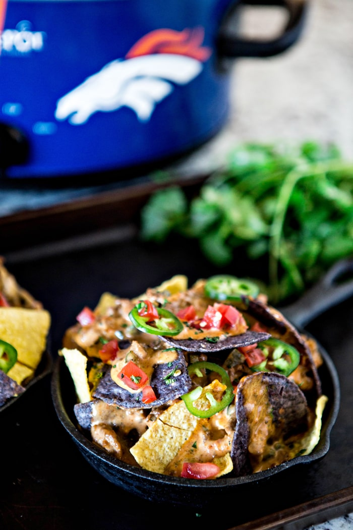 mini skillet filled with tortilla chips and crock pot queso