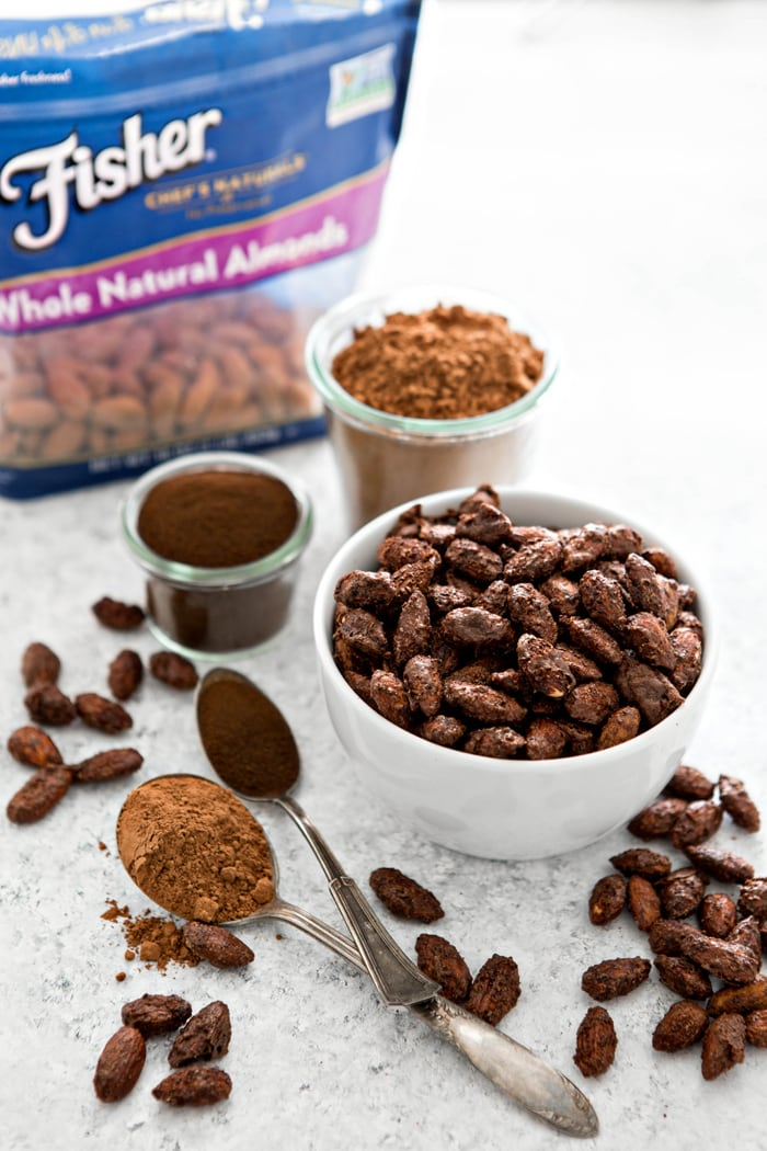 mocha roasted almonds in white bowl next to cocoa powder, espresso powder, and bag of nuts