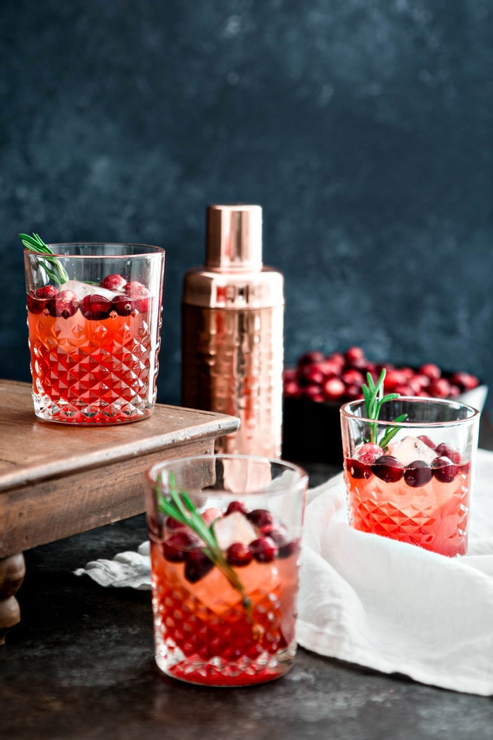 This Cranberry Rosemary Shrub Cocktail is the perfect Thanksgiving cocktail! A homemade cranberry shrub with hints of black pepper, rosemary, and cinnamon is combined with bourbon and seltzer for a festive and colorful drink!