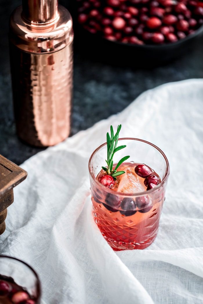 This Cranberry Rosemary Shrub Cocktail is the perfect Thanksgiving cocktail! A homemade cranberry shrub with hints of black pepper, rosemary, and cinnamon is combined with bourbon and seltzer for a festive and colorful drink.
