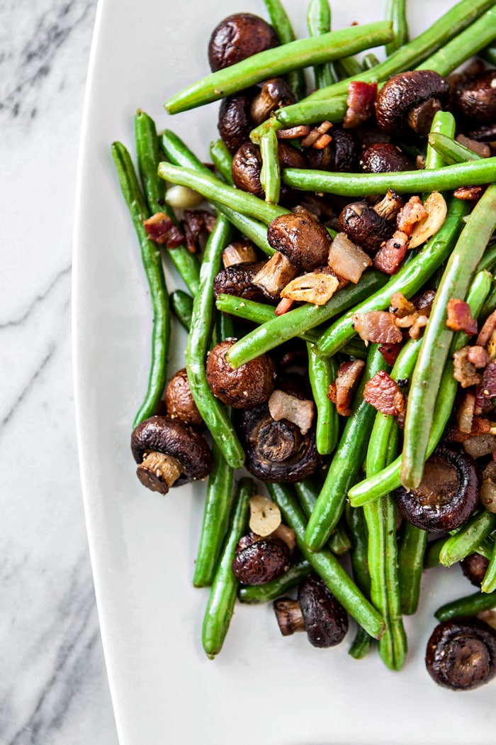 sauteed greens beans and mushrooms on white serving platter