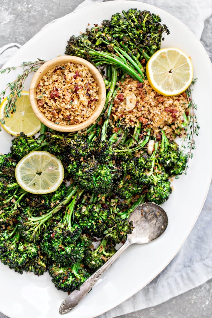 roasted broccolini with lemon slices, bread crumbs, and spoon on white serving platter