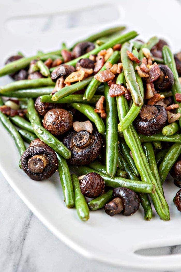 sauteed green beans with bacon, garlic, and balsamic mushrooms on white platter