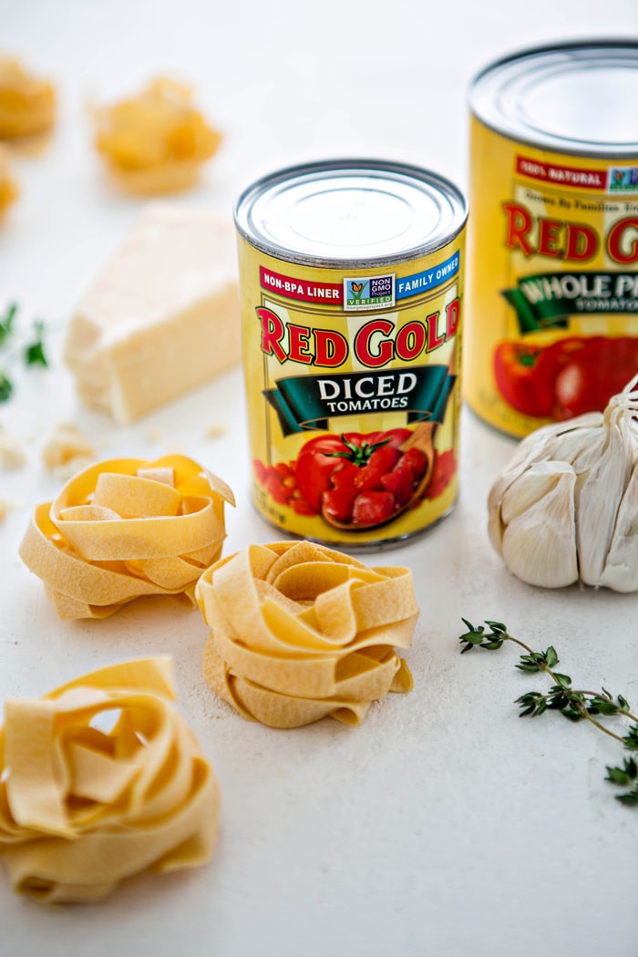 three bundles of fresh pasta next to canned tomatoes