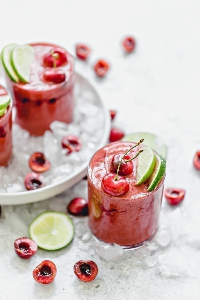 Cherry Limeade Slush in a clear glass surrounded by ice with fresh limes and cherries