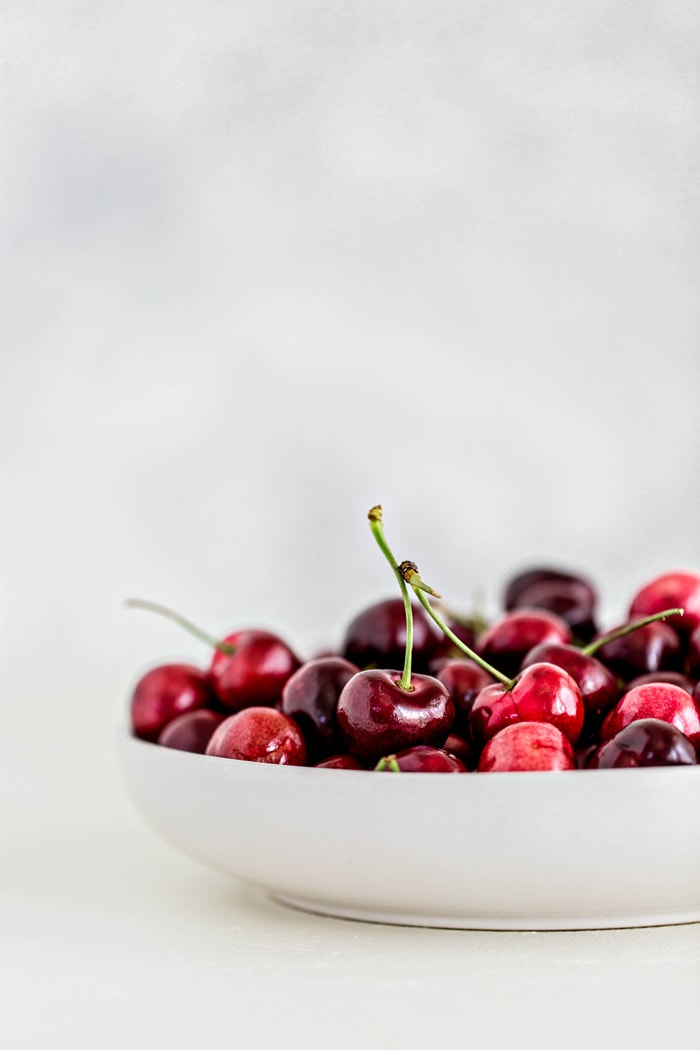 fresh cherries in a white bowl