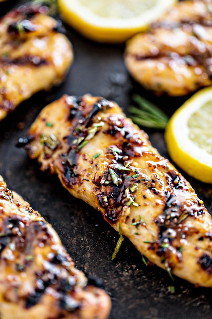 grilled chicken tenderloins on a black background with a lemon slice
