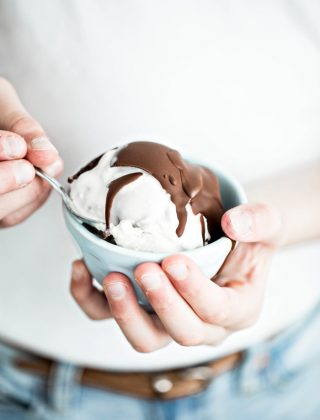 girl holding a bowl of ice cream with chocolate topping