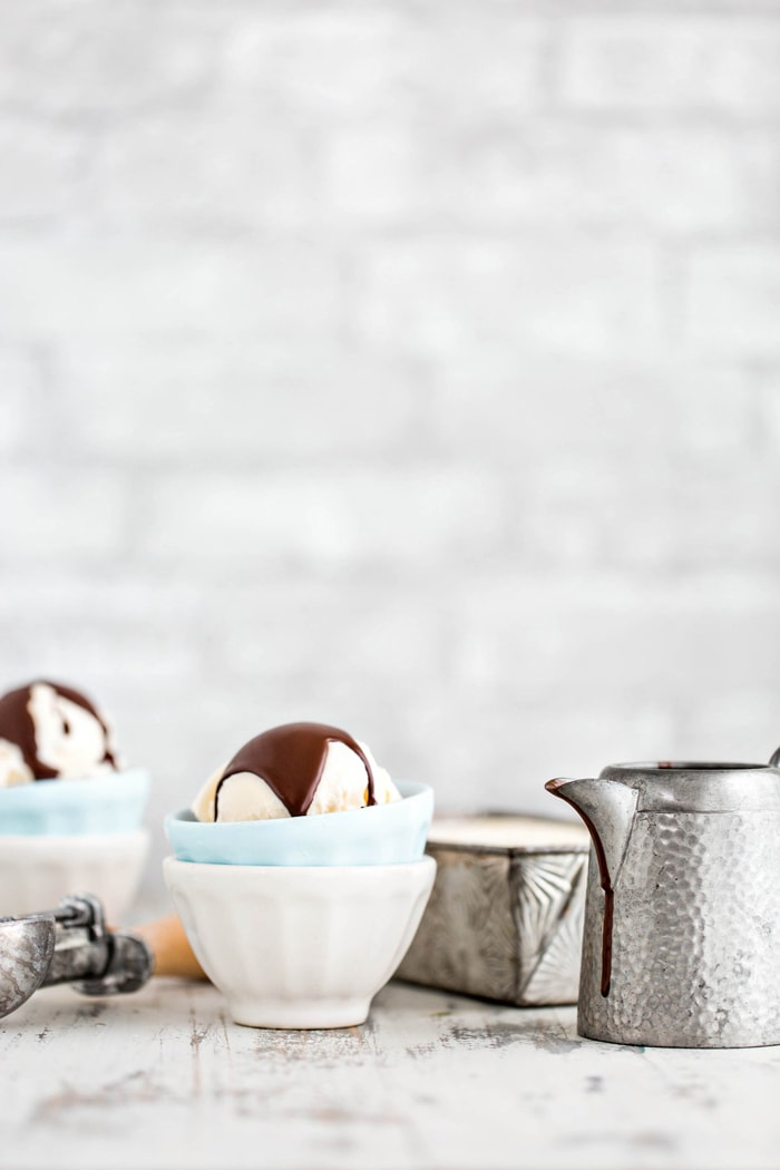 two bowls of vanilla ice cream with chocolate topping in front of a grey brick wall
