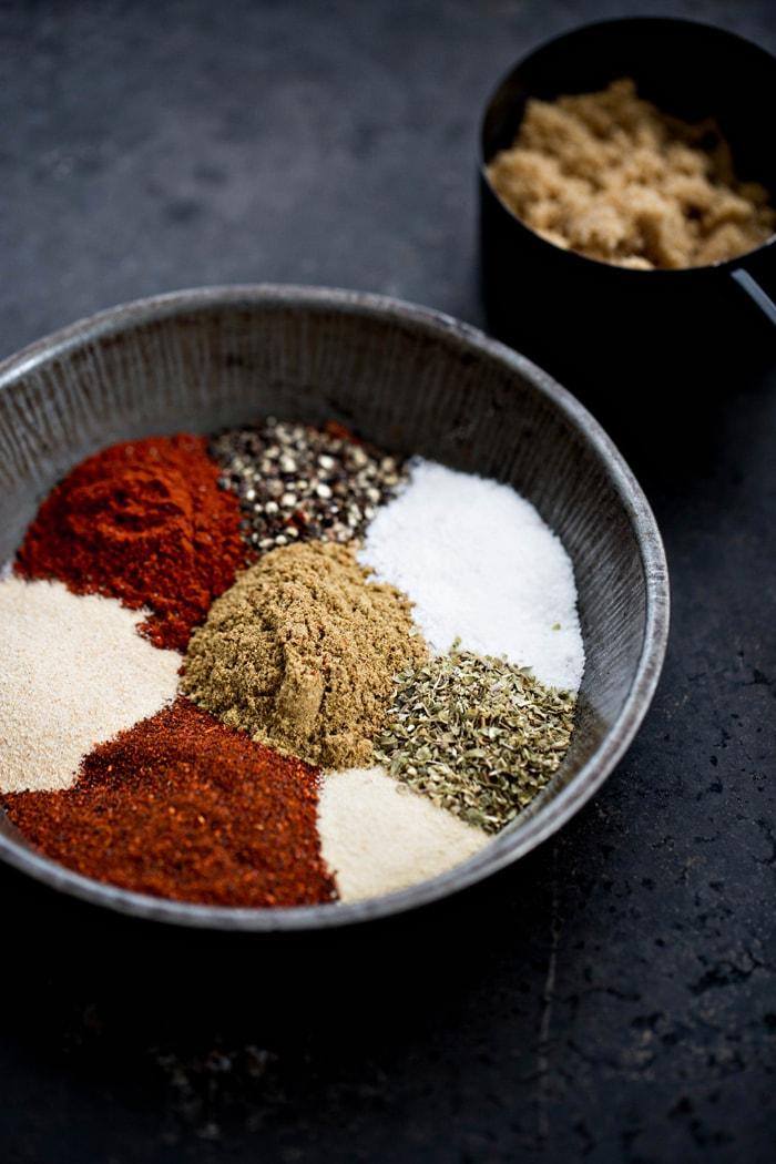 bowl of ingredients to make homemade pork rub on a dark background
