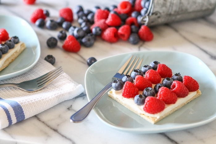 picture of fruit pizza with rows of raspberries and blueberries