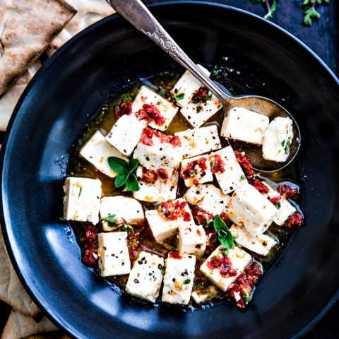black bowl with marinated feta surrounded by pita chips