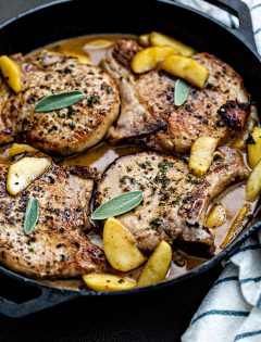pork chops with sage in and apples in a cast iron skillet