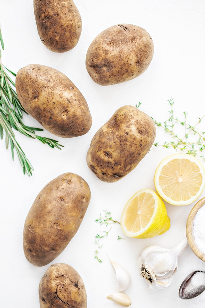 potatoes and rosemary on a white background