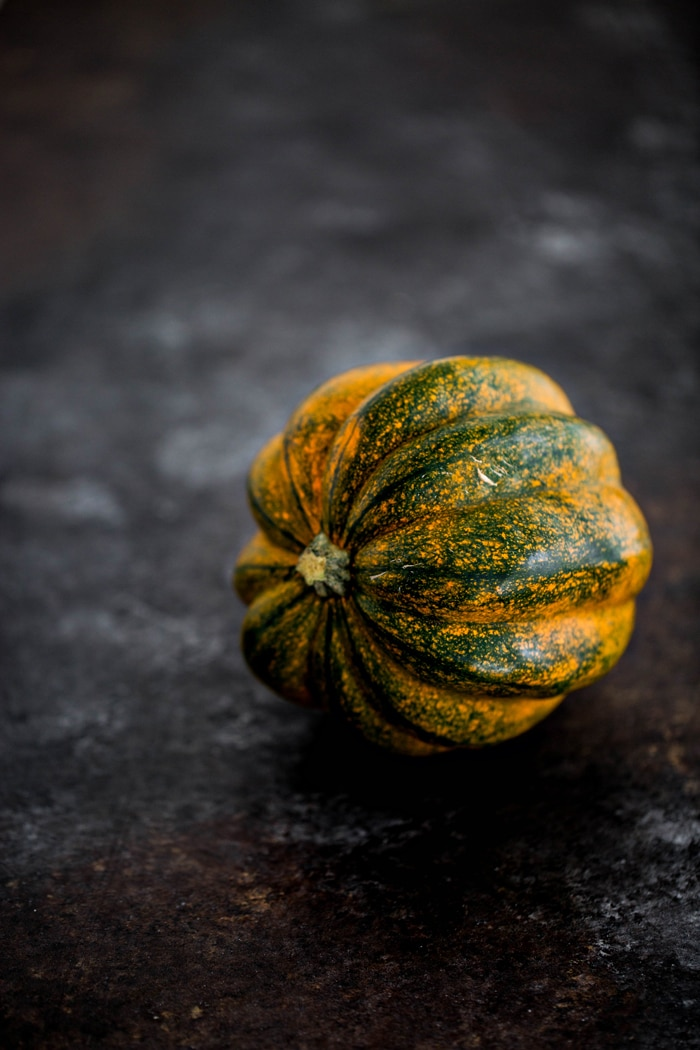 photo of a whole acorn squash on dark background