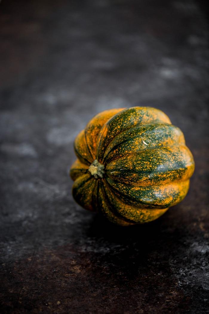 photo of a whole acorn squash on dark background