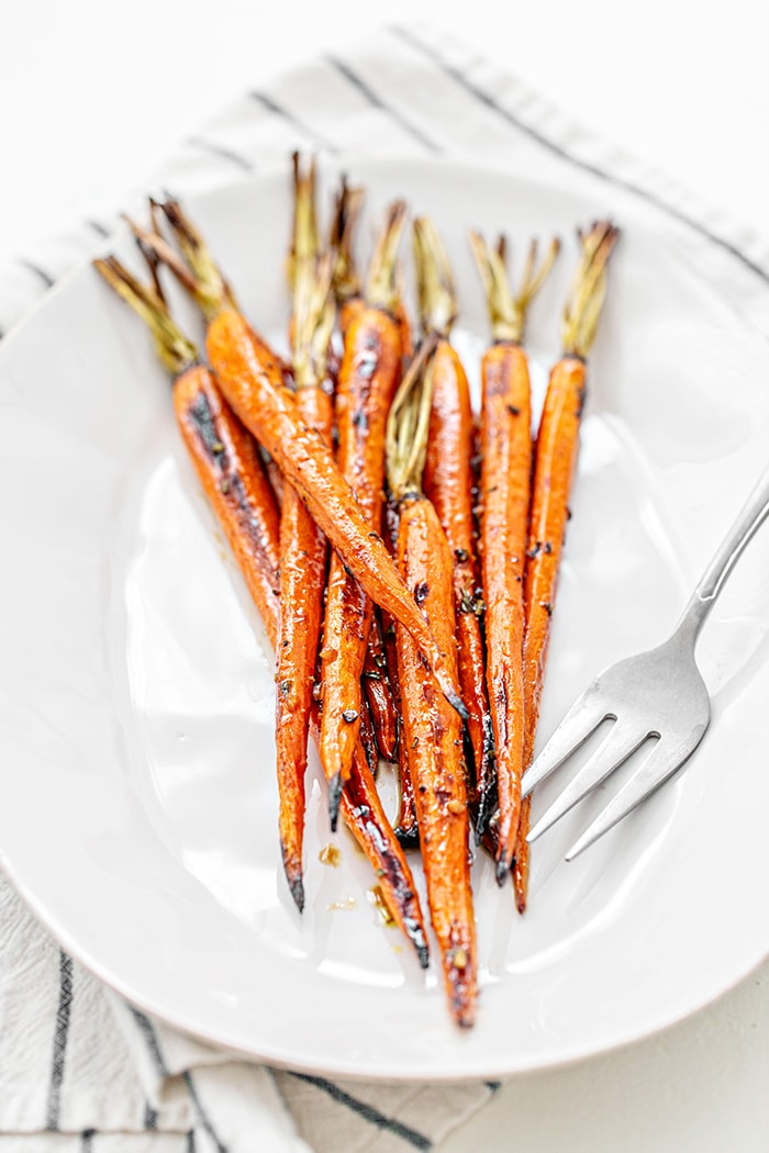 whole balsamic roasted carrots on a white plate