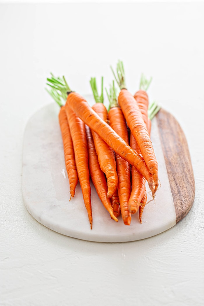 whole carrots on a marble platter