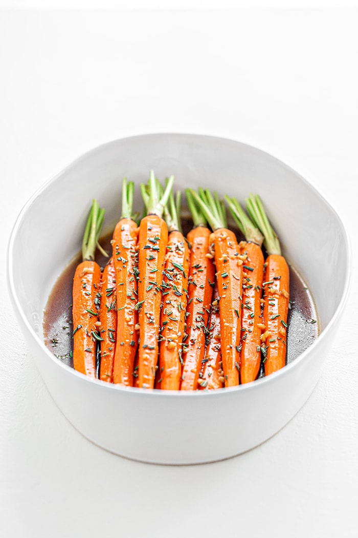whole carrots in a white bowl