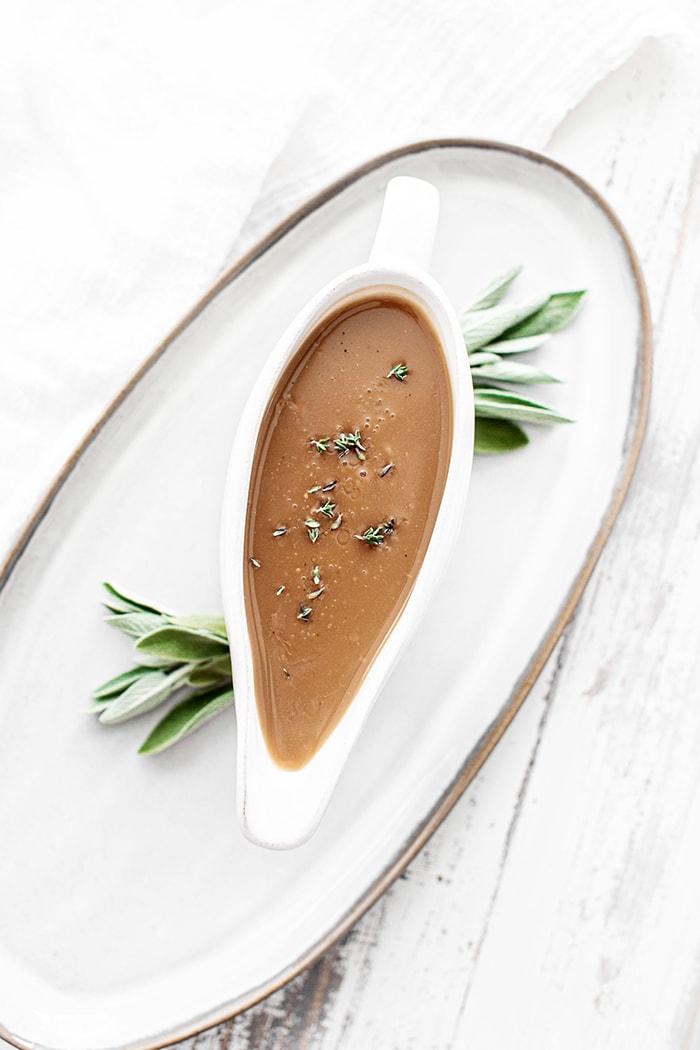 turkey gravy with sage in a white gravy boat