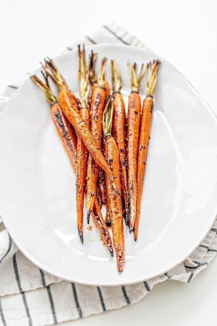 whole roasted carrots on white plate