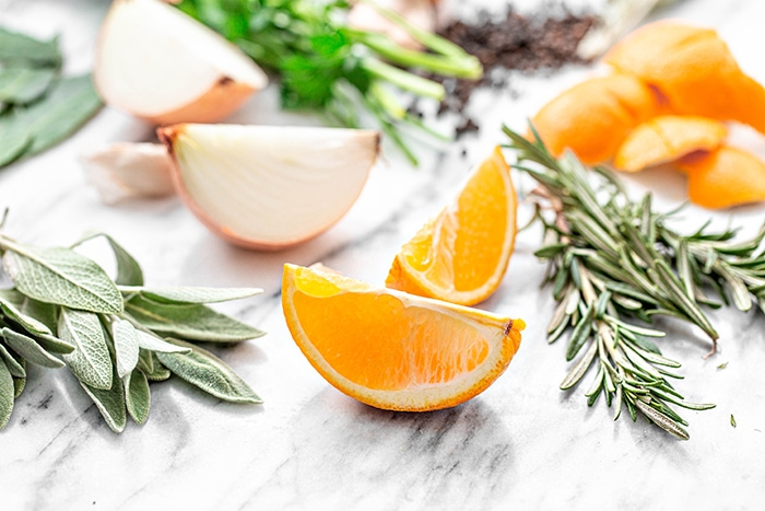 photo of oranges and fresh herbs on white background