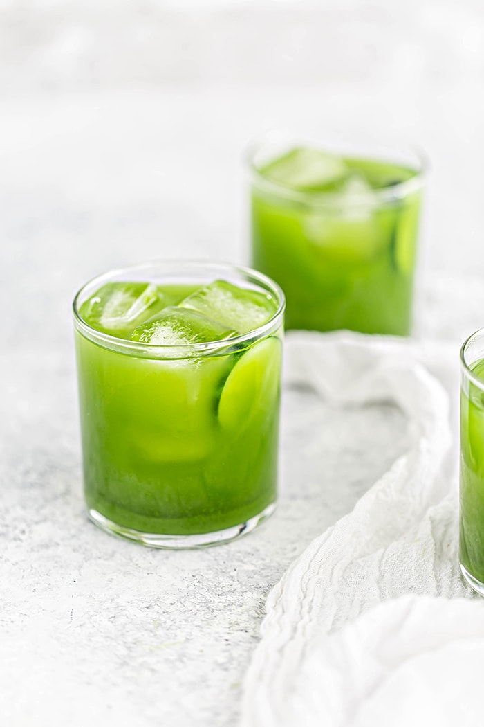 3 glasses of green juice spinach juice recipe on white background