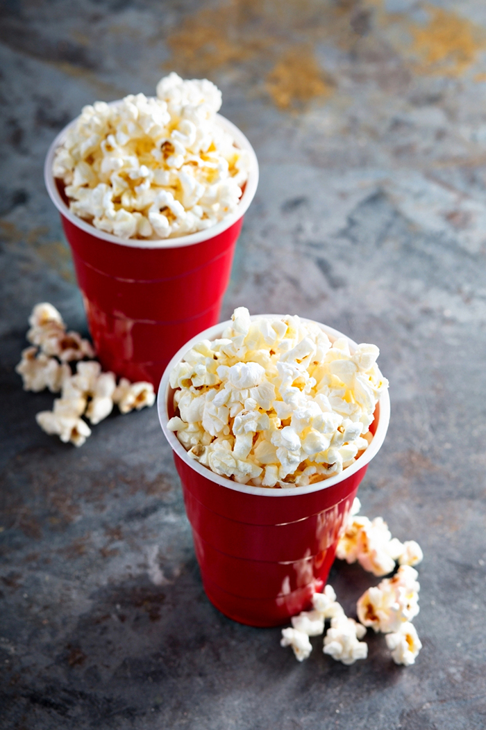 2 red cups with popcorn in them